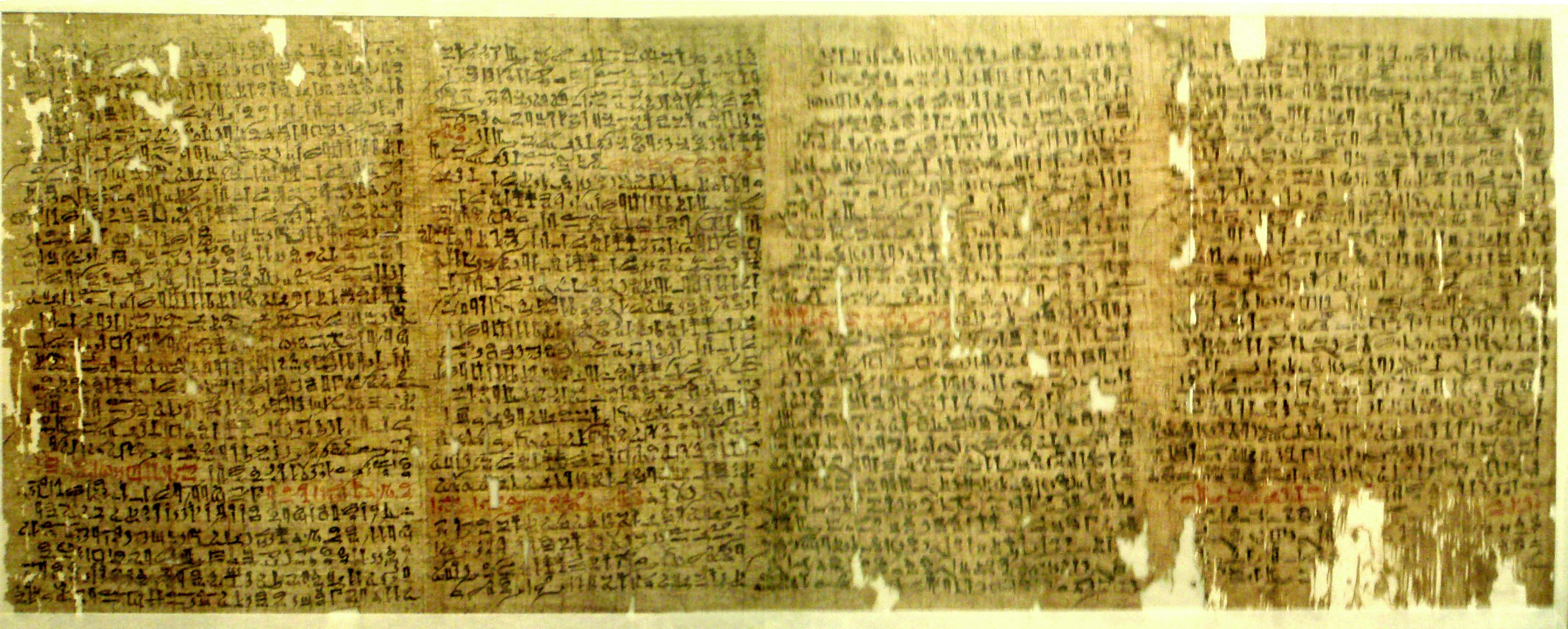 Фрагментированный папирус с немного порванными краями и иератическим почерком в красных чернилах