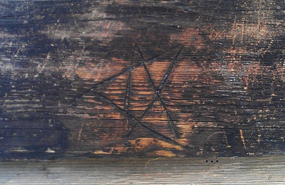 An apotropaic marking of a pentagram on a farmhouse building at the Niemalä tenant farm, now located at Seurasaari open air museum. These markings provided a rudimentary form of home protection.