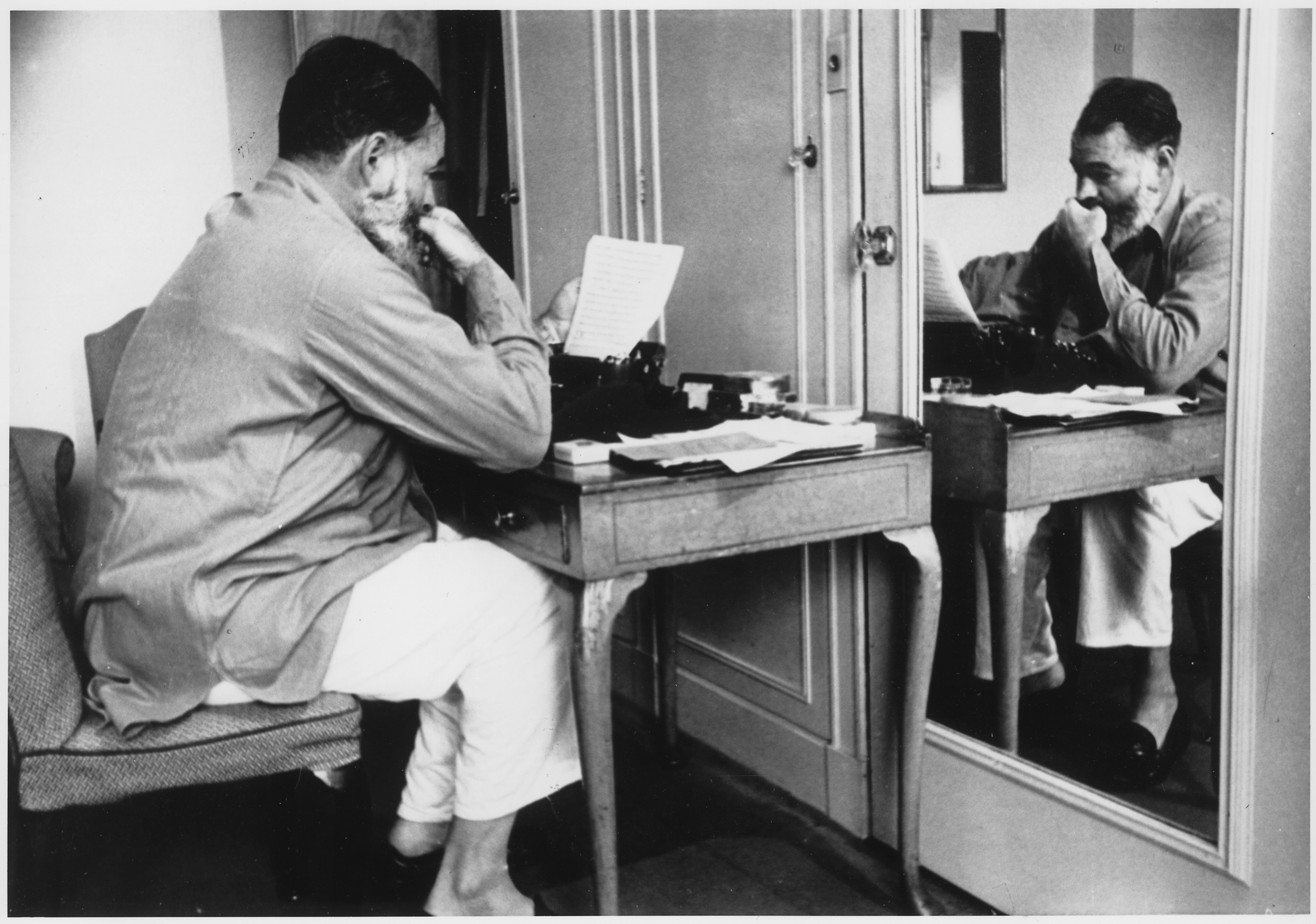 Black and white image of a man sitting at a desk in front of the mirror, reading something