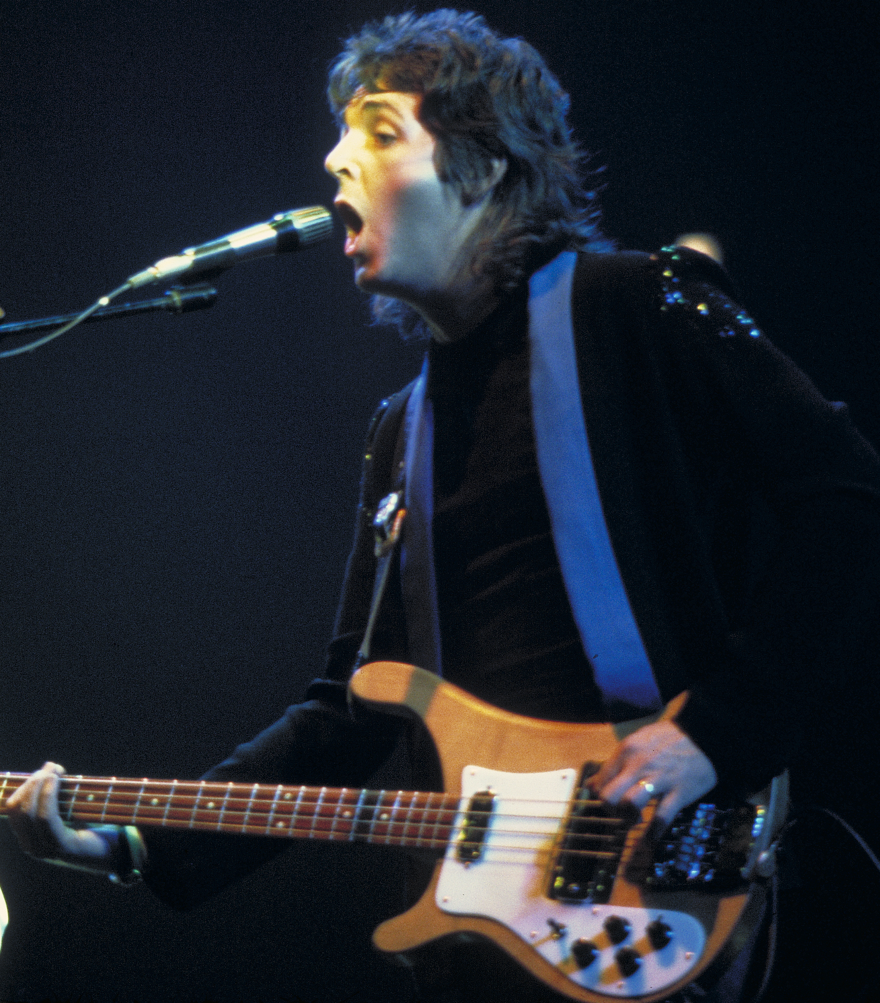 Coloured image of a long-haired McCartney in the 1970s playing a guitar.