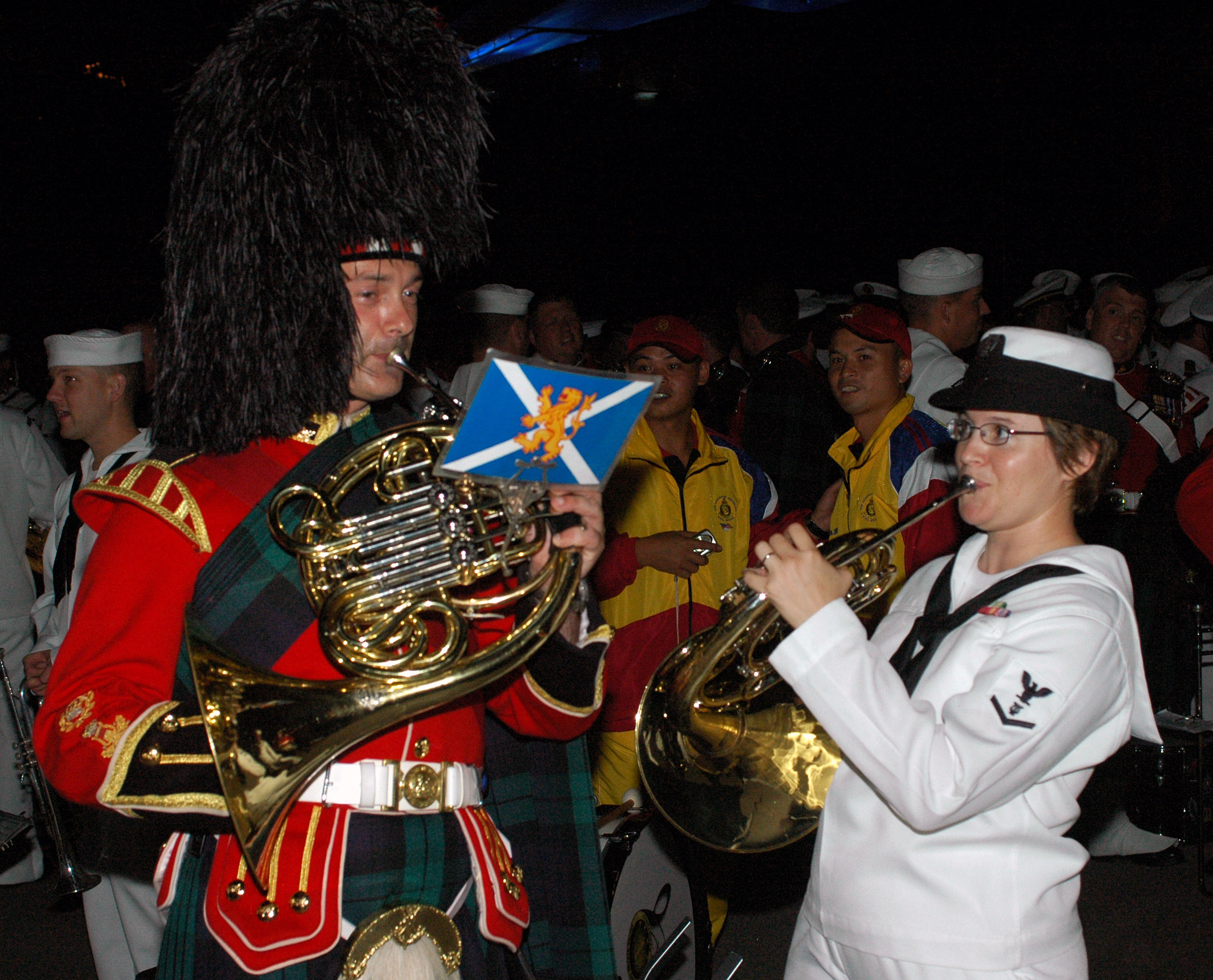 US Navy 070907-N-5174T-005 Musician 3rd Class Helena Giammarco, a Pacific Fleet band member, plays the French horn backstage with a friend from the Royal Regiment of Scotland following the second night of performances at the Ku