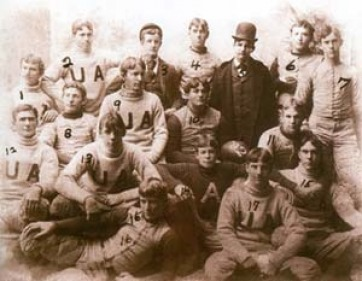 "Black & white image illustrating 17 American football players in their uniforms with both a single ""A"" and ""UA"" visible."
