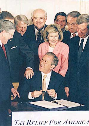"Signing the 2001 legislation that came to be known as the ""Bush tax cuts."""