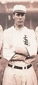 "A man in a white baseball uniform with an overlapping ""STL"" on the left breast stands on a baseball field with his arms crossed."