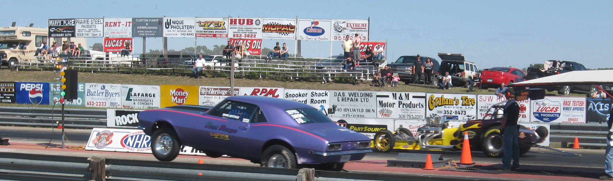 Camaro performing a wheelie during drag racing.
