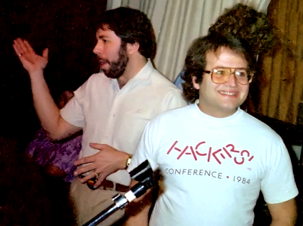 Steve Wozniak and Andy Hertzfeld standing and talking at an informal group meeting