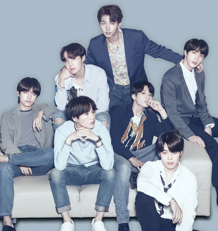 BTS band poses in gray and blue scale on couch.