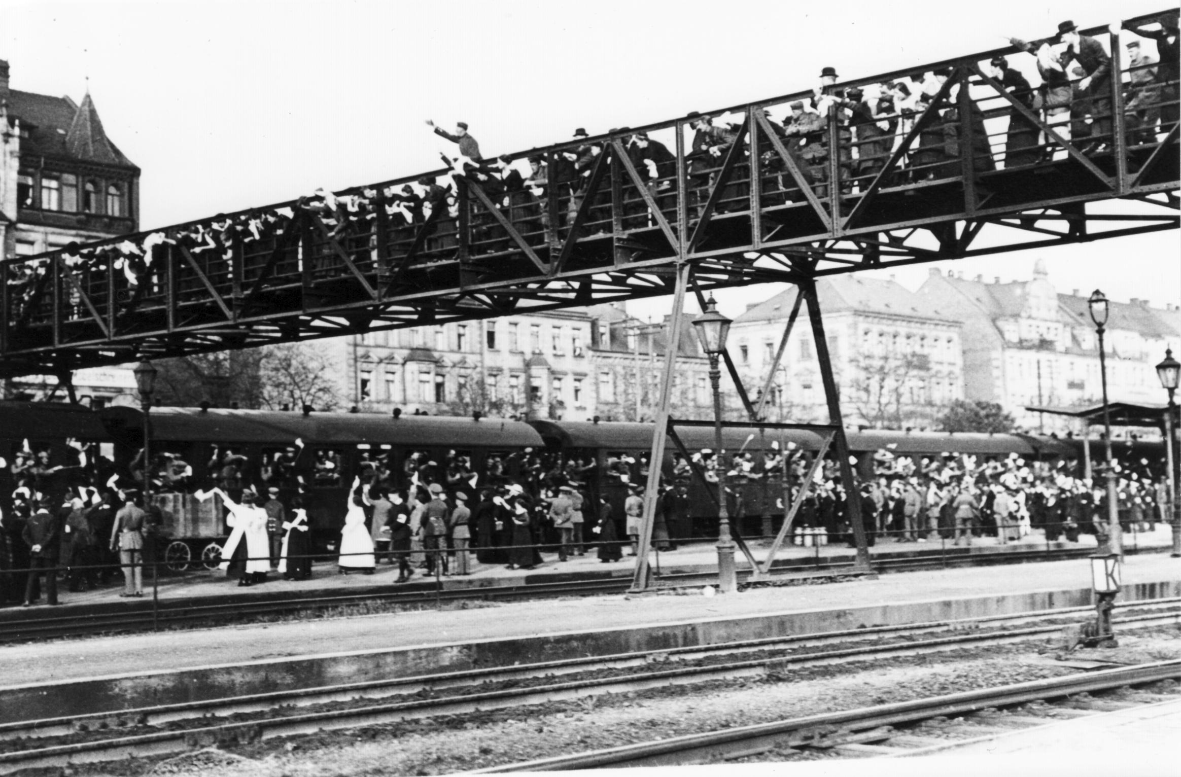 """Bayerische Truppen verlassen am 7. und 8. August 1914 """"unter nicht enden wollenden Hurra- und Abschiedsgrüßen""""[5] den Bahnhof von Fürth (deutsche Postkarte)"""