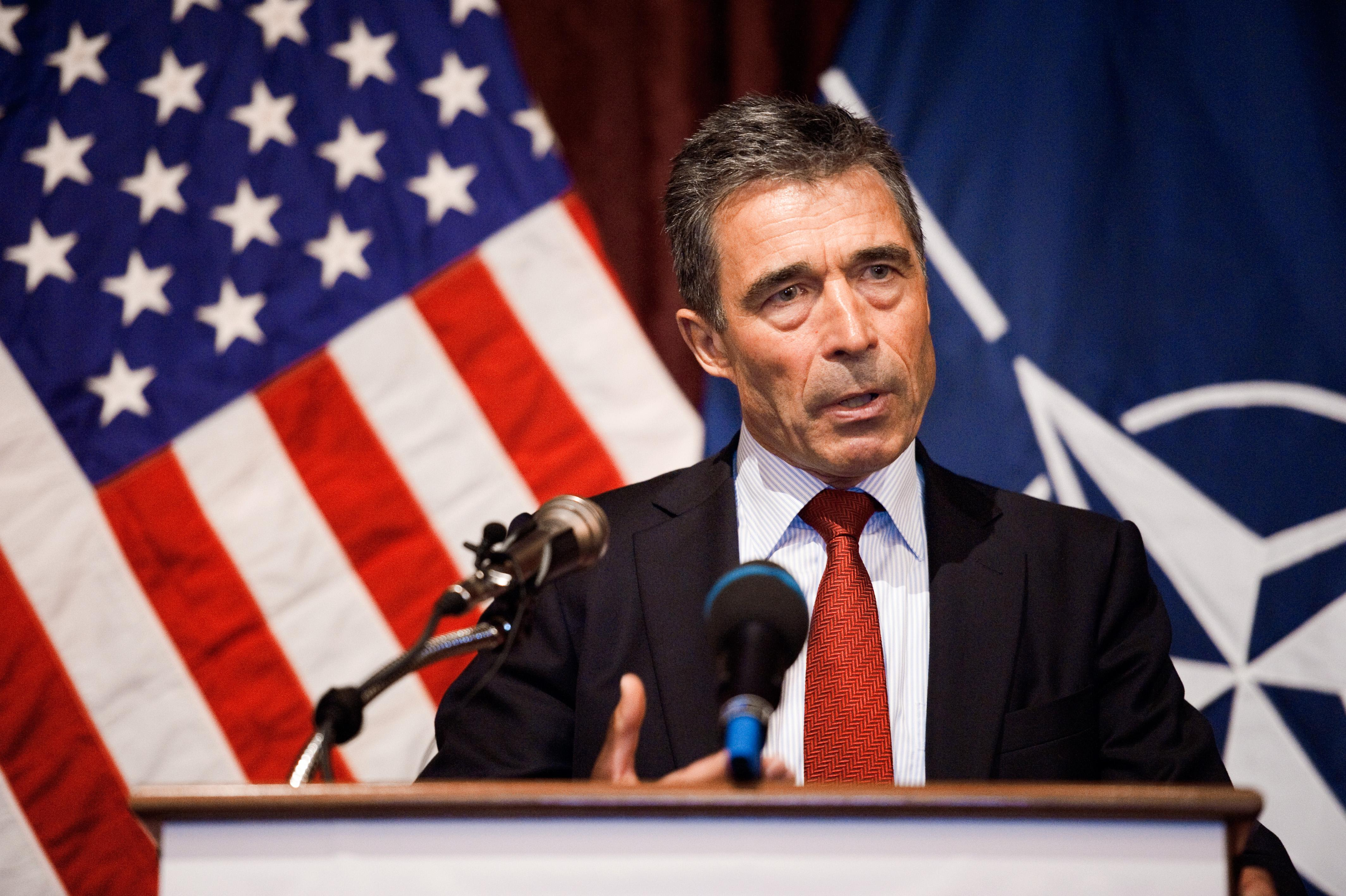 An older man in a suit speaking at a podium in front of two flags.