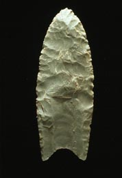 """A Clovis blade with medium to large lanceolate spear-knife points. Side is parallel to convex and exhibit careful pressure flaking along the blade edge. The broadest area is near the midsection or toward the base. The base is distinctly concave with a characteristic flute or channel flake removed from one or, more commonly, both surfaces of the blade. The lower edges of the blade and base is ground to dull edges for hafting. Clovis points also tend to be thicker than the typically thin later stage Folsom points. Length: 4–20 cm/1.5–8 in. Width: 2.5–5 cm/1–2"