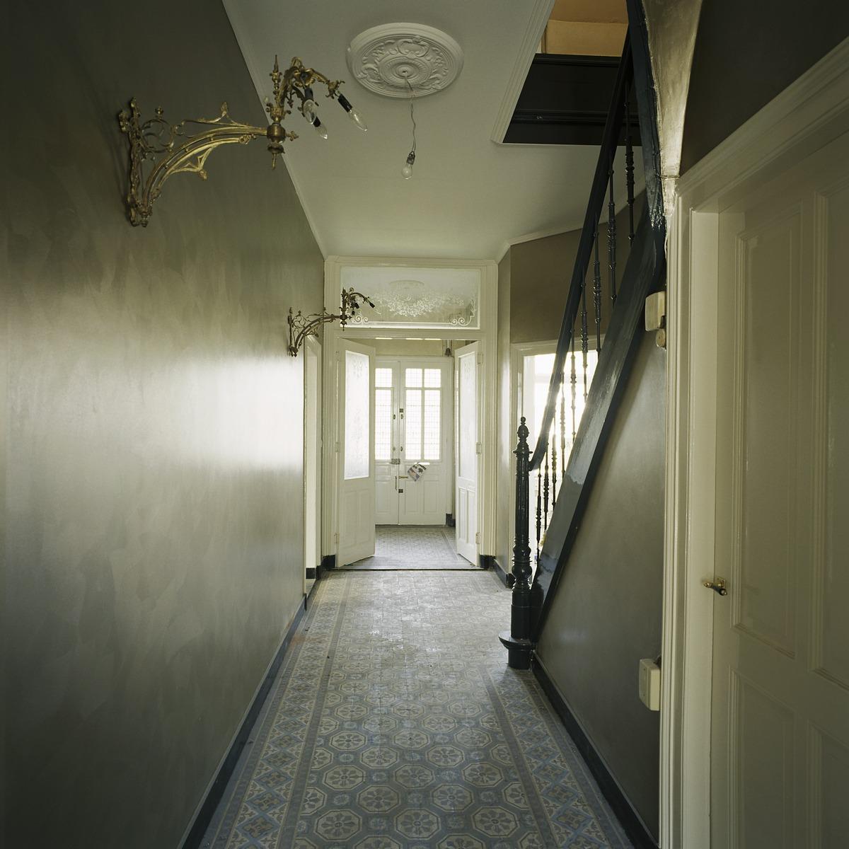 File interieur overzicht van de gang op de begane grond met tegelvloer en met rechts de trap - Gang met trap ...