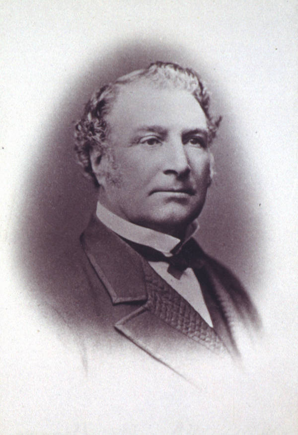 Stately looking middle aged caucasian fellow in black and white daguerreotype photo, with curly hair and stiff upright white collar