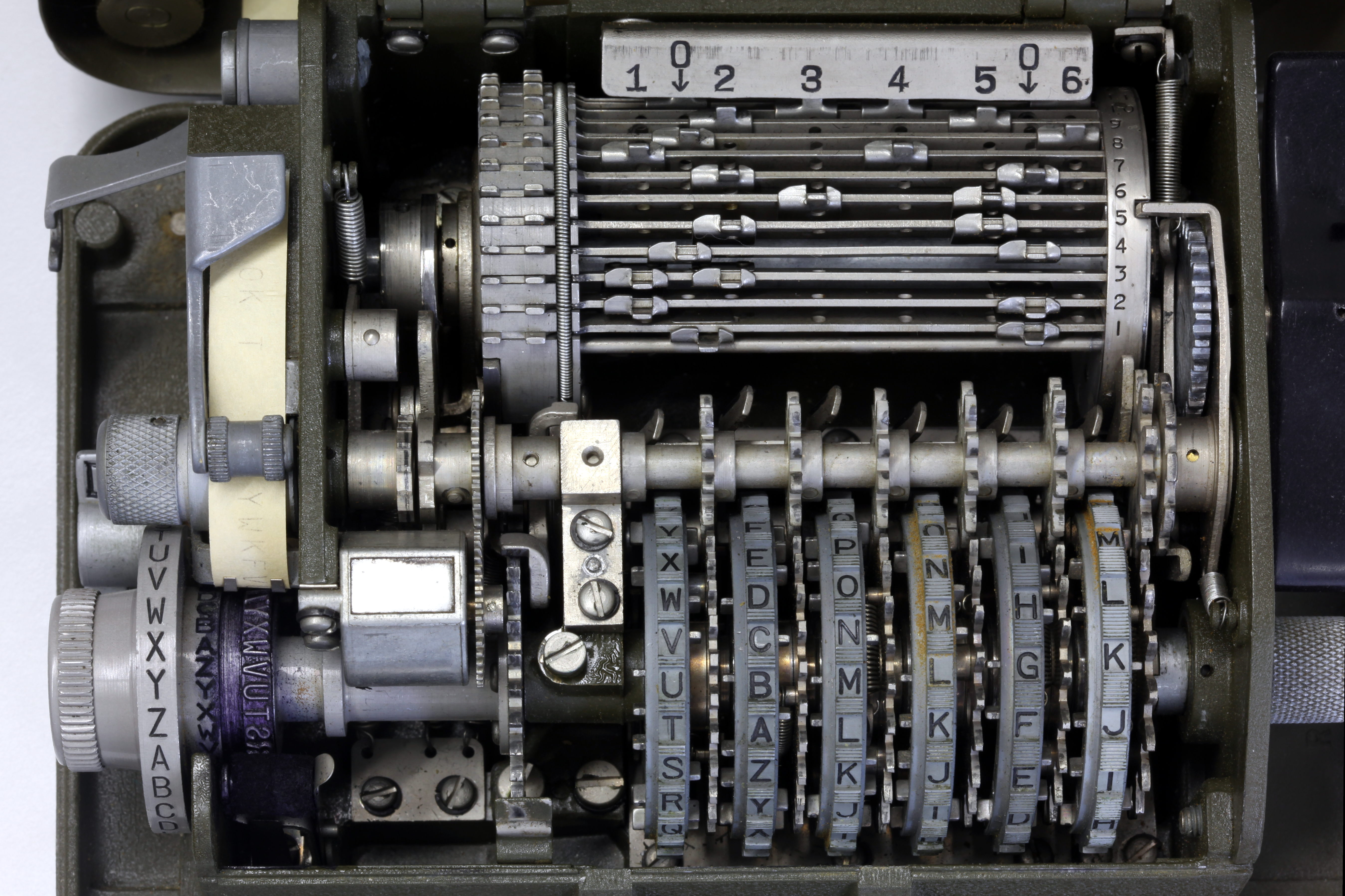An Intermediate Gear Unit Center Meshes With Gears Adjoining Each Key Wheel Visible To The Left Of Image Are Paper Tape And Typewheel That Print