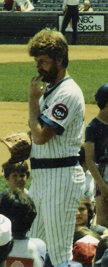 White man with beard and mustache standing on a baseball field with his hand in his mouth, wearing a white Cubs uniform with blue pinstripes and no cap.