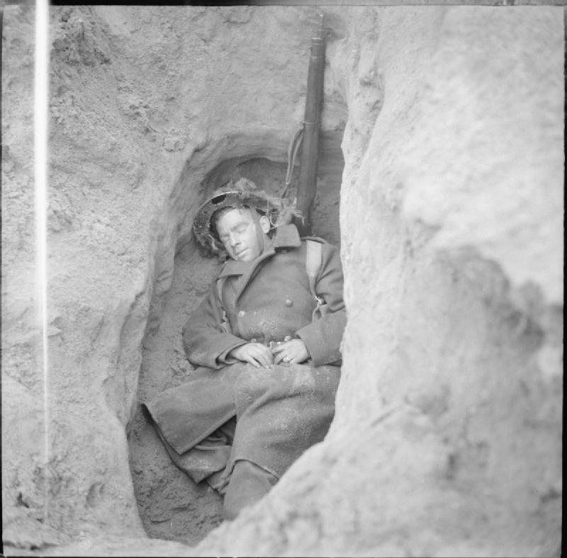 An infantryman asleep in his foxhole