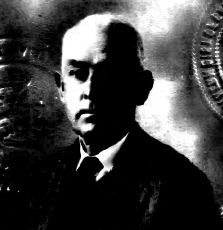 Image: A black-and-white photo of a middle-aged Anglo man with pale receding hair and a somewhat serious expression, wearing a dark tie and sport coat, but no eyeglasses in this picture.