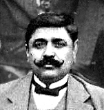 Black and white portrait photograph of a moustachioed man dressed in a dinner jacket and bow tie