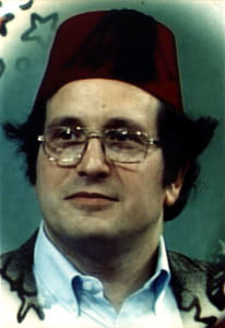 Photograph of head of a man wearing glasses and a dark burgundy fez hat