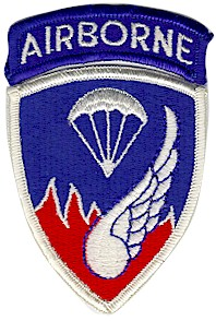 "A blue shoulder patch saying ""AIRBORNE"" and containing images of a parachute and a wing superimposed over fire"