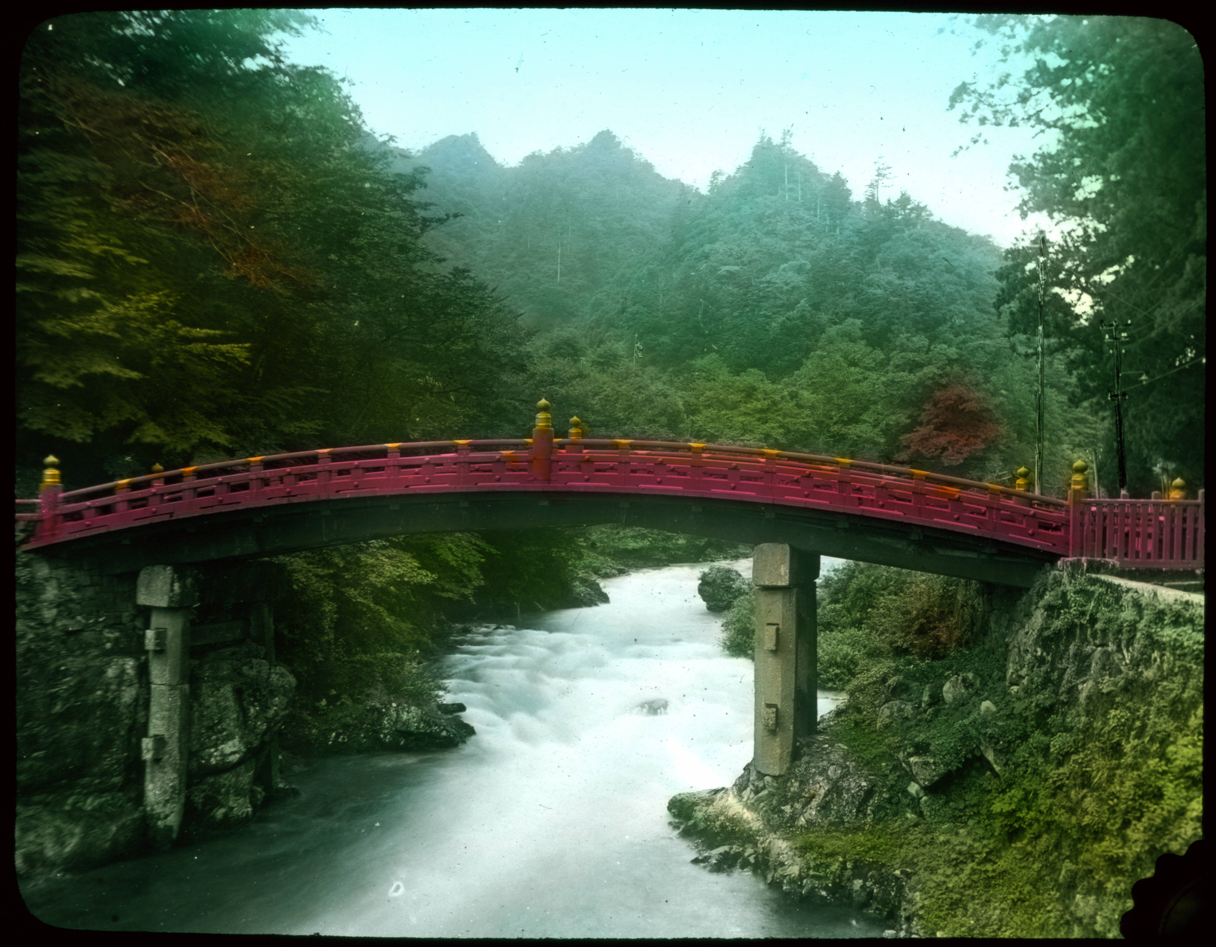 File:Curved red wooden bridge over river; forest in ...