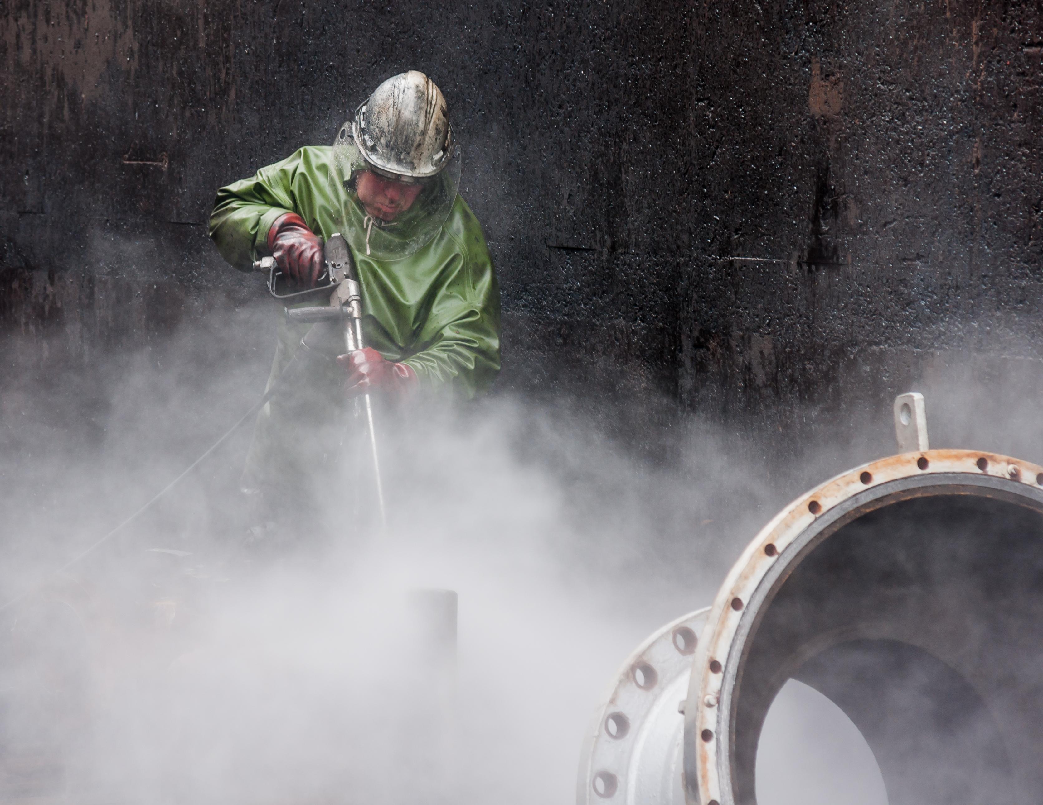 High-Pressure-Cleaning-with-Personal-Protective-Equipment-02.jpg Deutsch: Köln, Deutschland: Industrielle Hochdruckreinigung von Druckgeräteteilen