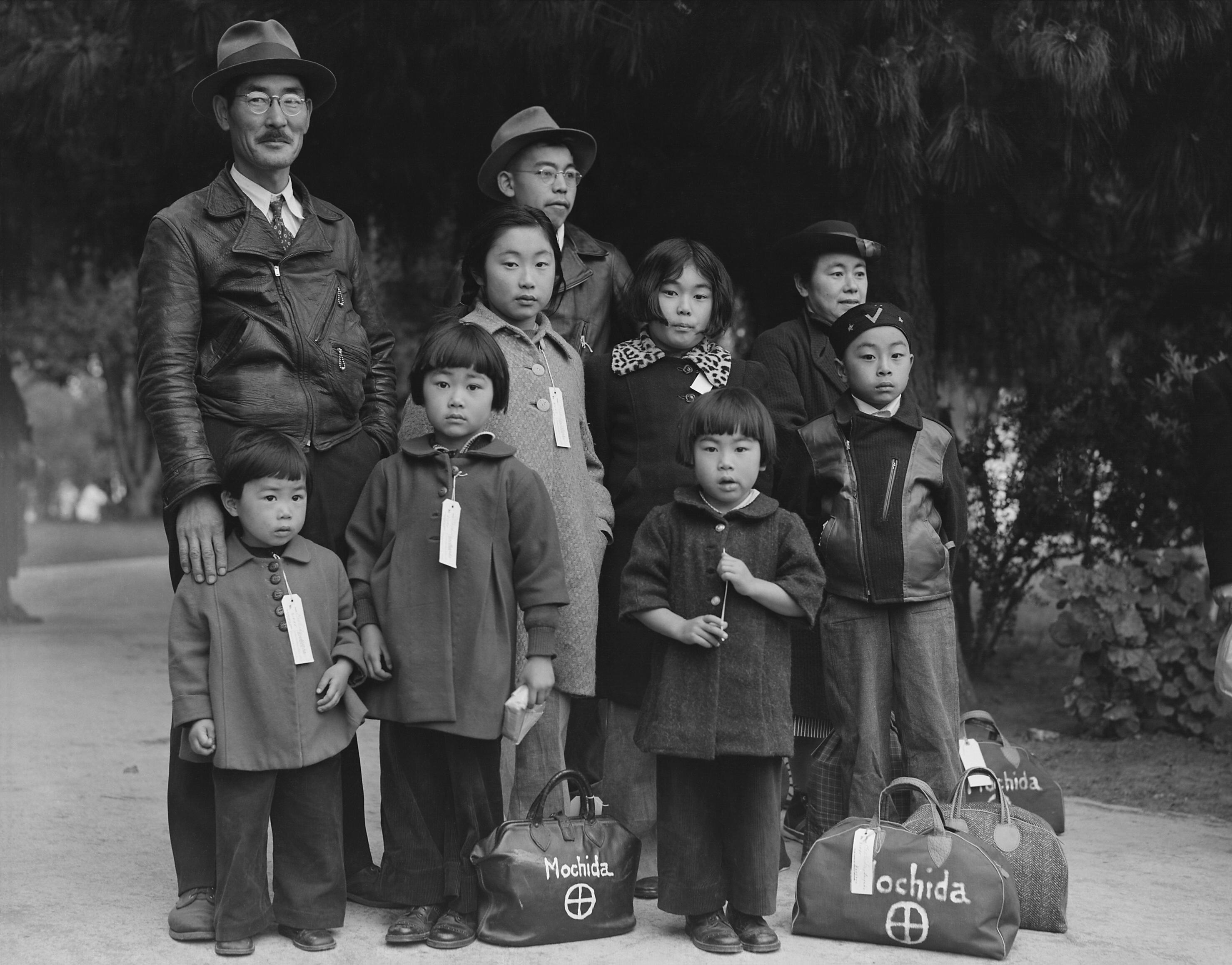 Members of the Mochida family awaiting evacuation bus. Mochida operated a nursery and five greenhouses on a two-acre site in Eden Township. Hayward, California. 8 May 1942 (Dorothea Lange) [2958x2316]