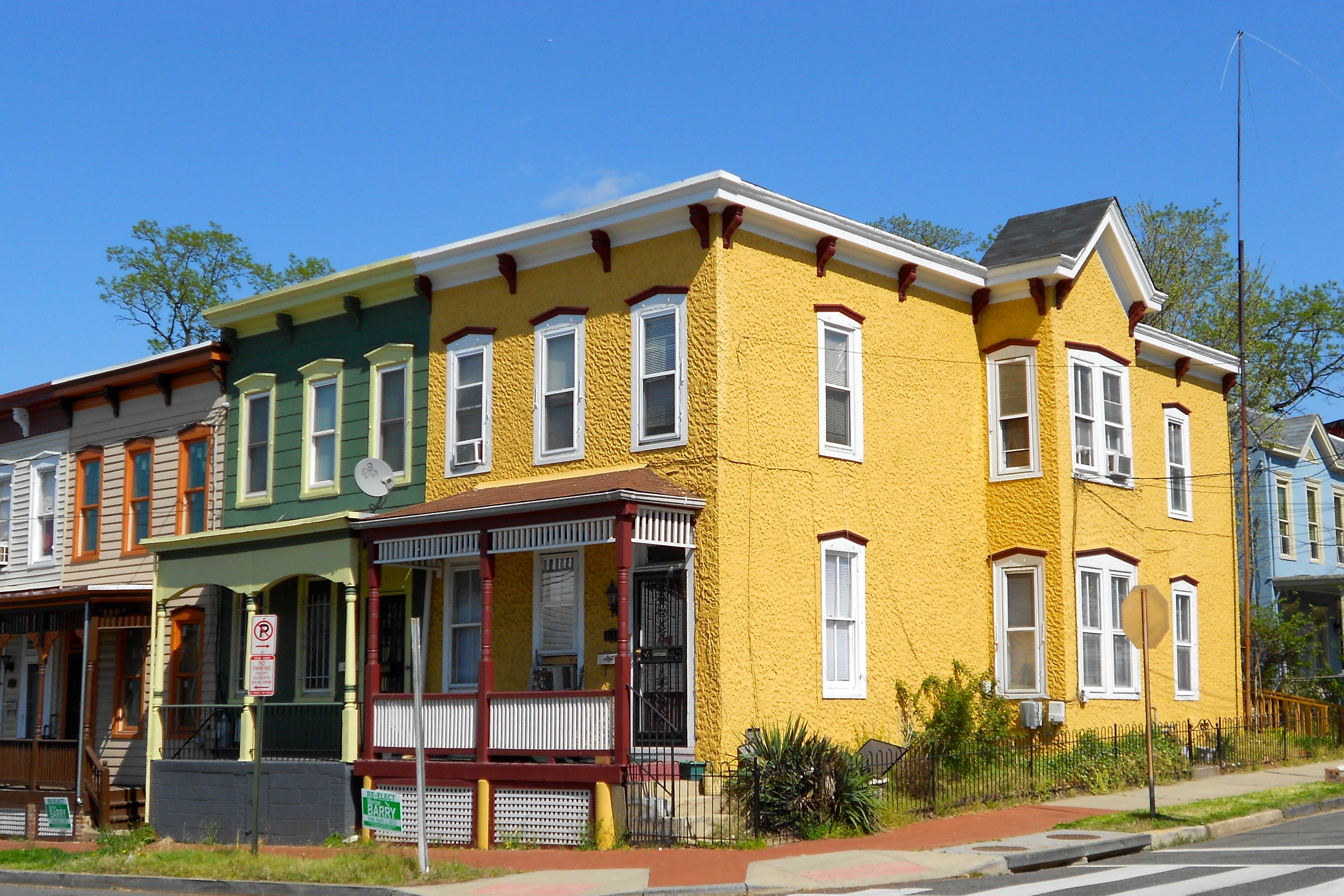 Four houses at 13th Street and W Street, SE in the Anacostia Historic District. The four houses are yellow, green, brown/orange, and white. The houses have porches.