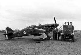 Single-engined military monoplane being refuelled by truck on airfield