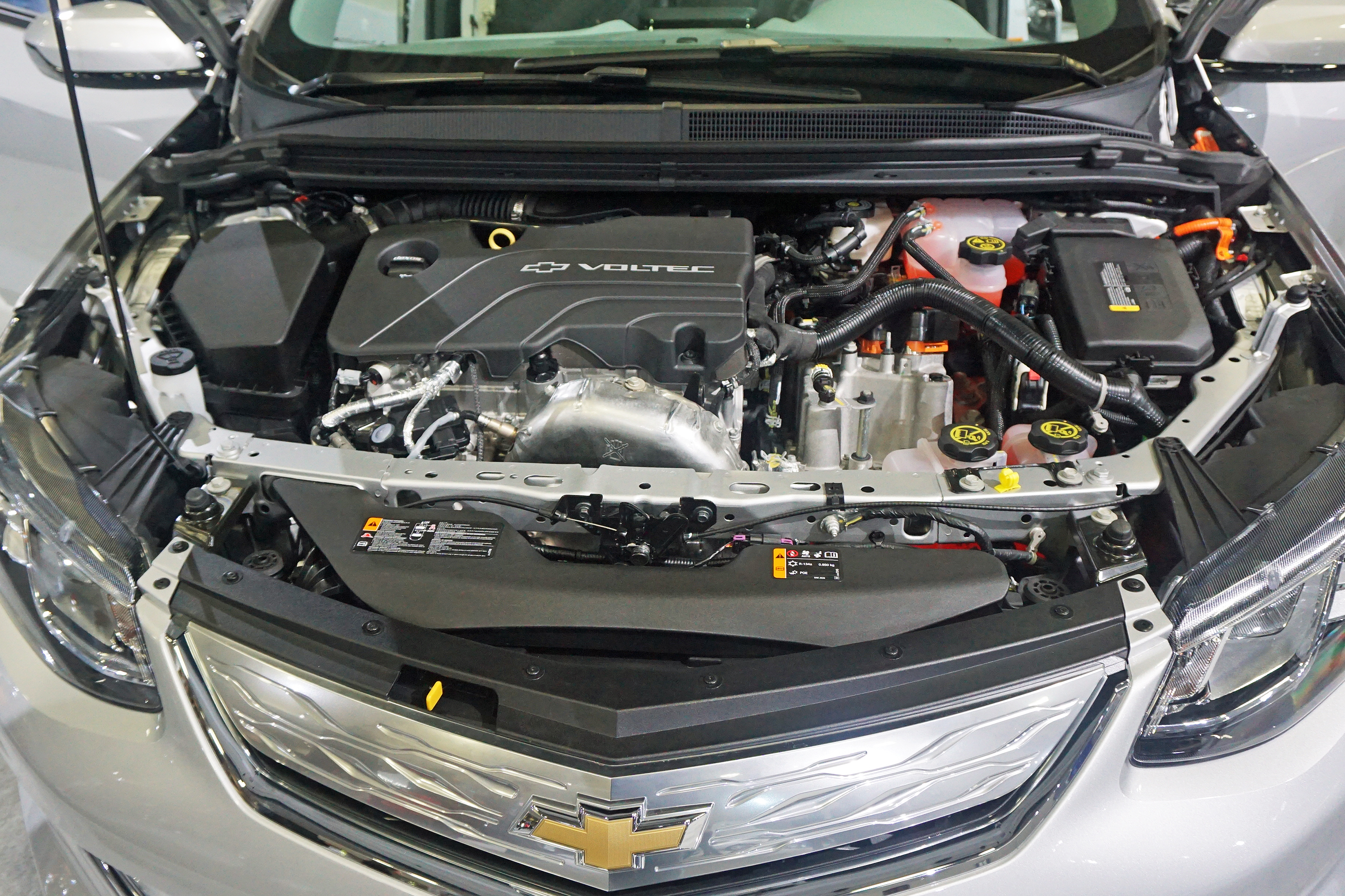 chevrolet volt second generation voltec 1 5l gasoline powered engine left and power inverter on top of the traction electric motor right