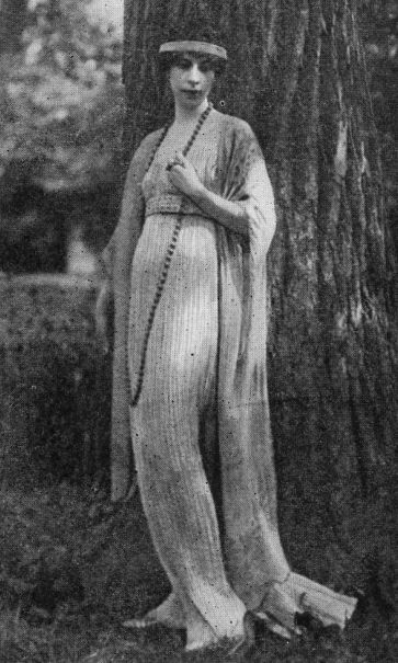 Mrs. Cond Nast wearing one of the famous Fortuny tea gowns. This one has no tunic but is finely pleated, in the Fortuny manner, and falls in long lines, closely following the figure, to the floor.