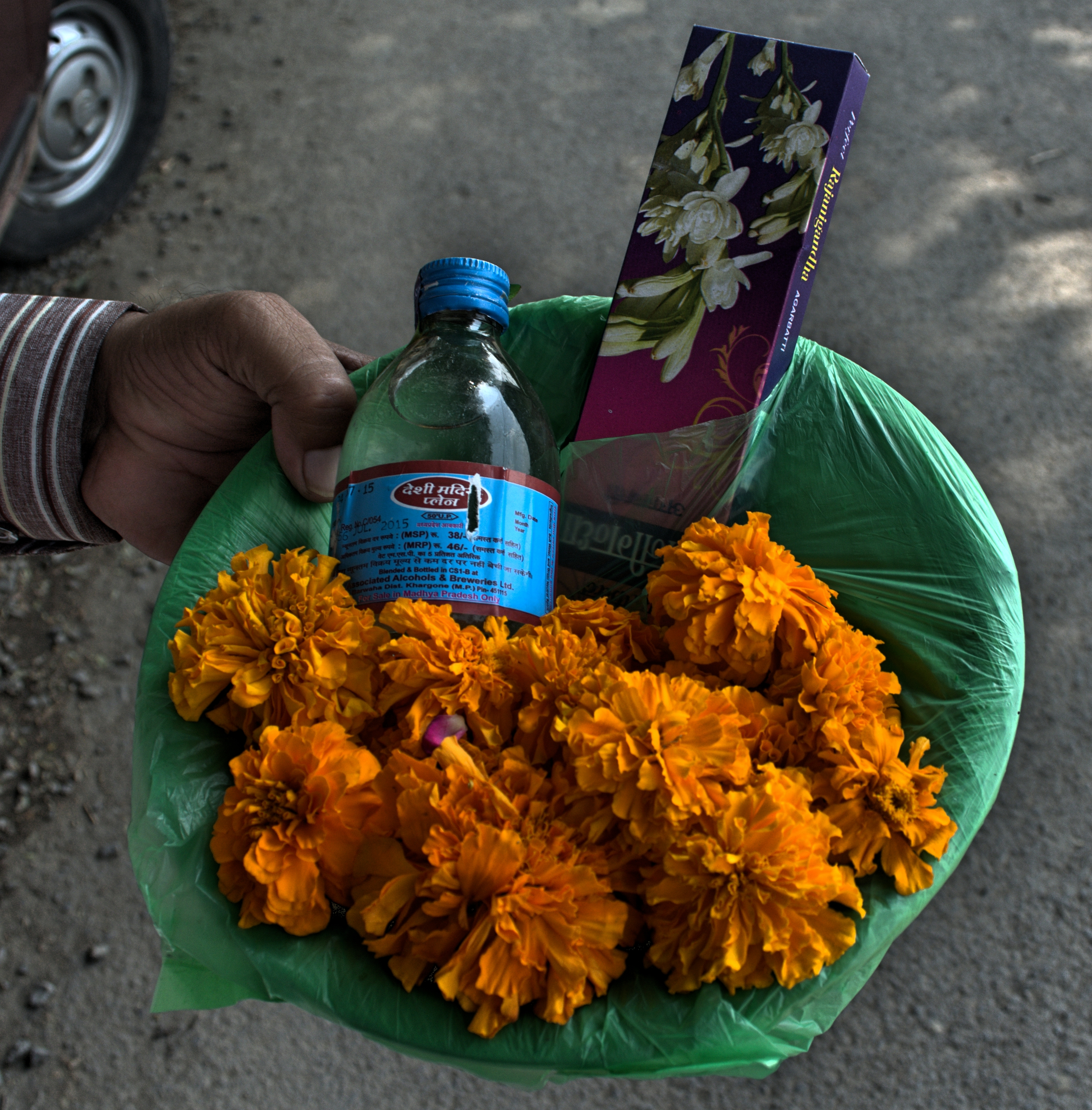 A typical basket of offerings, containing desi daru (country liquor), a pack of incense sticks and marigold flowers