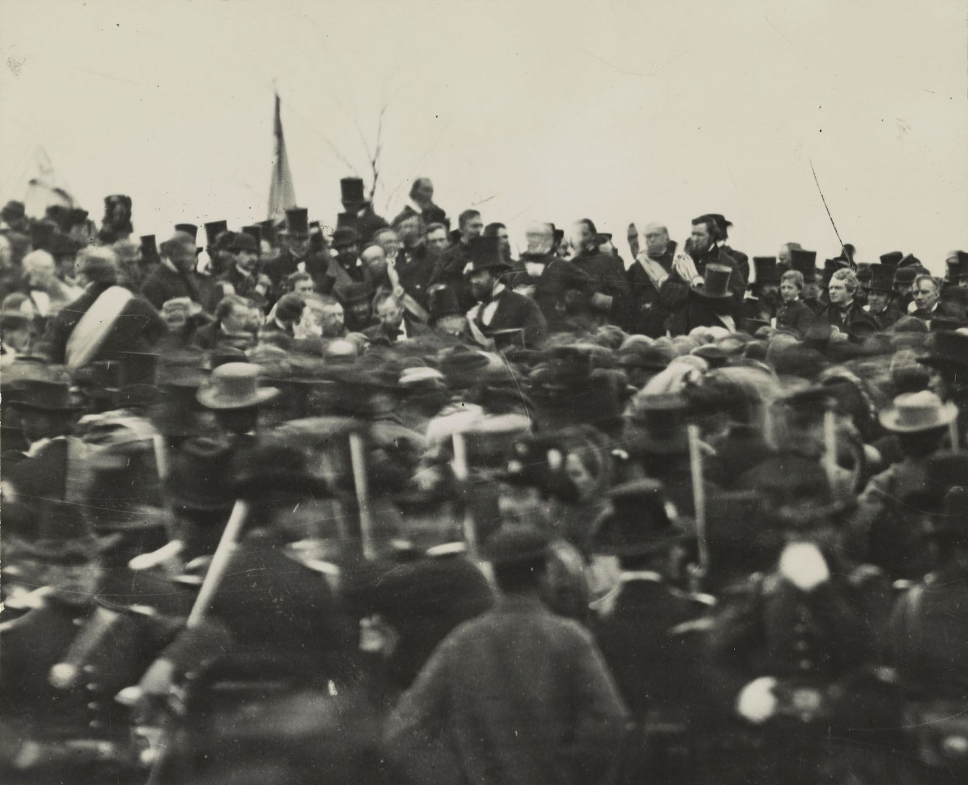 One of three known photos of Abraham Lincoln at the dedication of the Soldiers' National Cemetery in Gettysburg, Pennsylvania, on November 19, 1863. Made from the original glass plate negative at the National Archives which had lain unidentified for fifty-five years until 1952 when Josephine Cobb recognized Lincoln in the image. To Lincoln's right is bodyguard Ward Hill Lamon. To his far left is Governor Andrew G. Curtin of Pennsylvania. The photograph is estimated to have been taken at about noontime, just after Lincoln arrived, before Edward Everett's arrival and about three hours before Lincoln gave his famous Gettysburg Address. 19 November 1863. Image by David Bachrach (1845-1921). This image (or other media file) is in the public domain because its copyright has expired. Source: https://commons.wikimedia.org/wiki/File:Lincolnatgettysburg.jpg