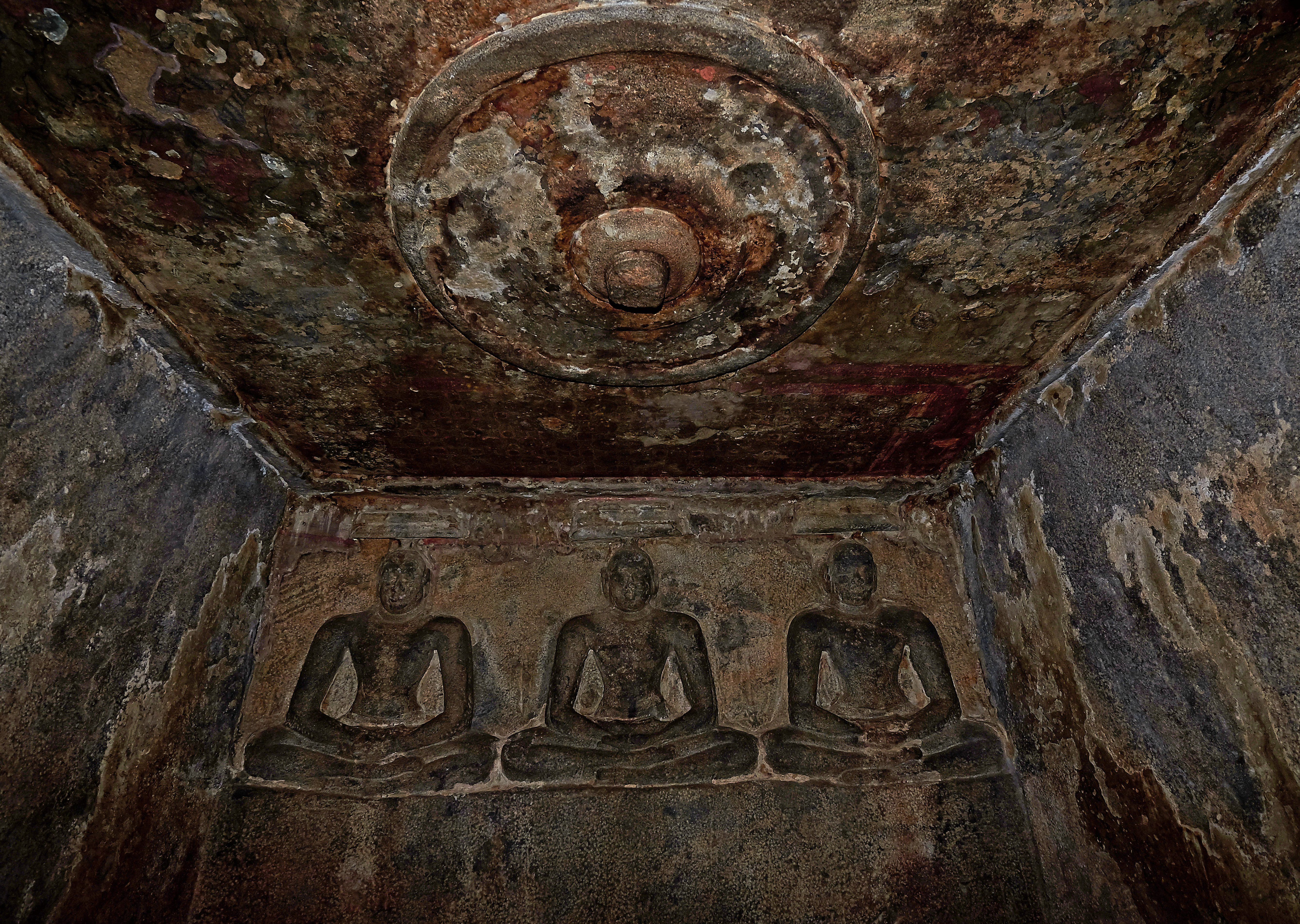 Three rock cut sculptures of Jain Tirthankaras inside the Sanctum at Sittannavasal