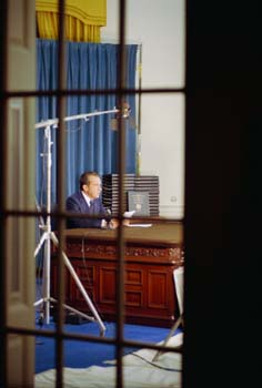 A view of President Nixon at the Wilson Desk as seen though a window into the Oval Office.
