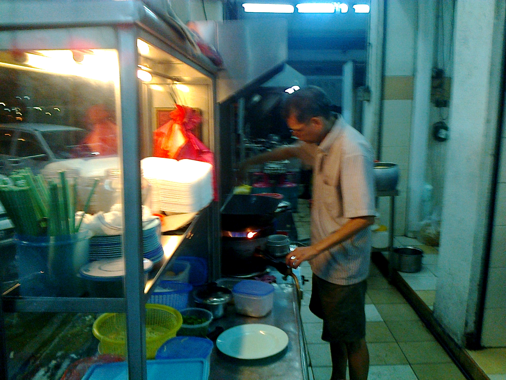 A cook making Char Kuey Teow, a type of flat noodles fried with fish cakes, cockles and bean sprouts.
