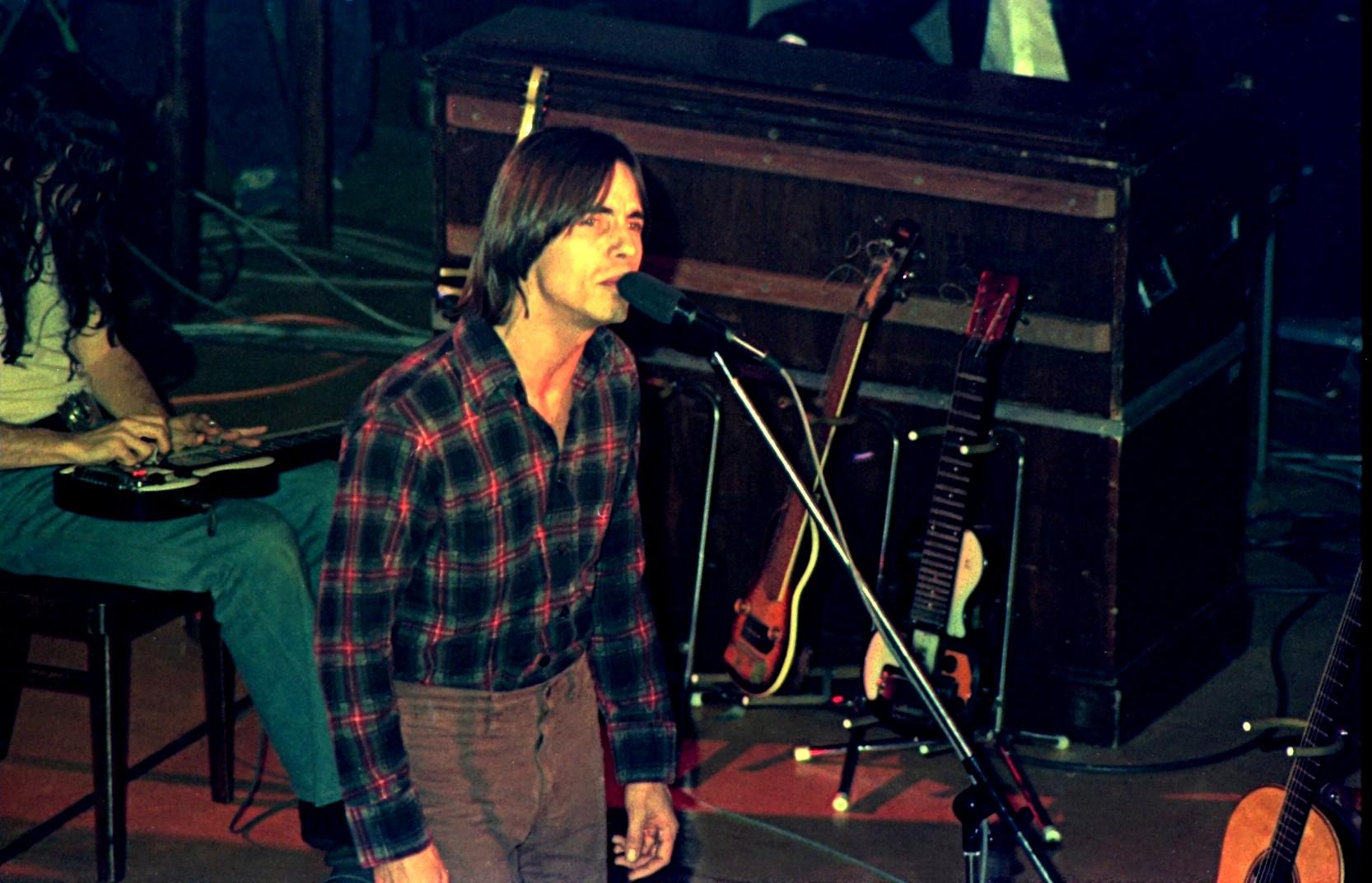 Browne en un concierto en 1976 en Hamburgo, Alemania, al micrófono con David Lindley, a quién se ve en la sombra a la izquierda del escenario tocando la guitarra lap steel.