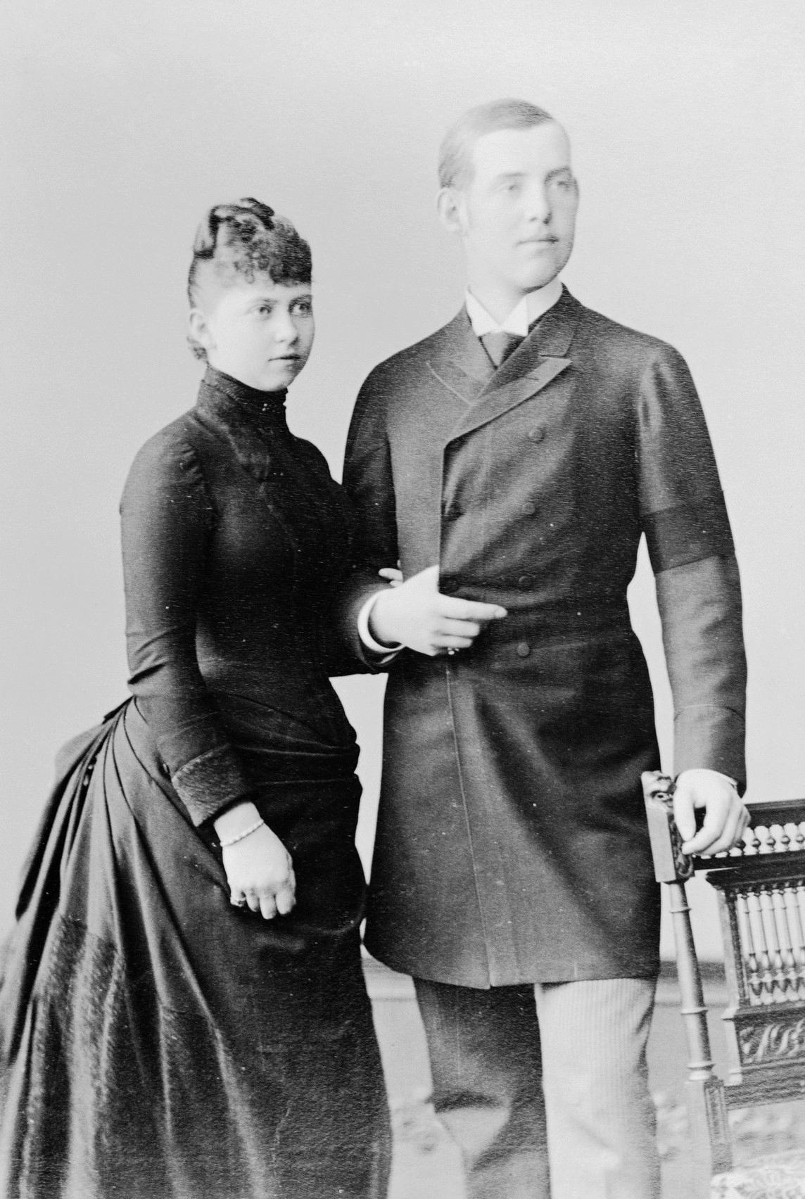 Photographie en noir et blanc d'une jeune femme portant une robe noire et d'un jeune homme en redingote.