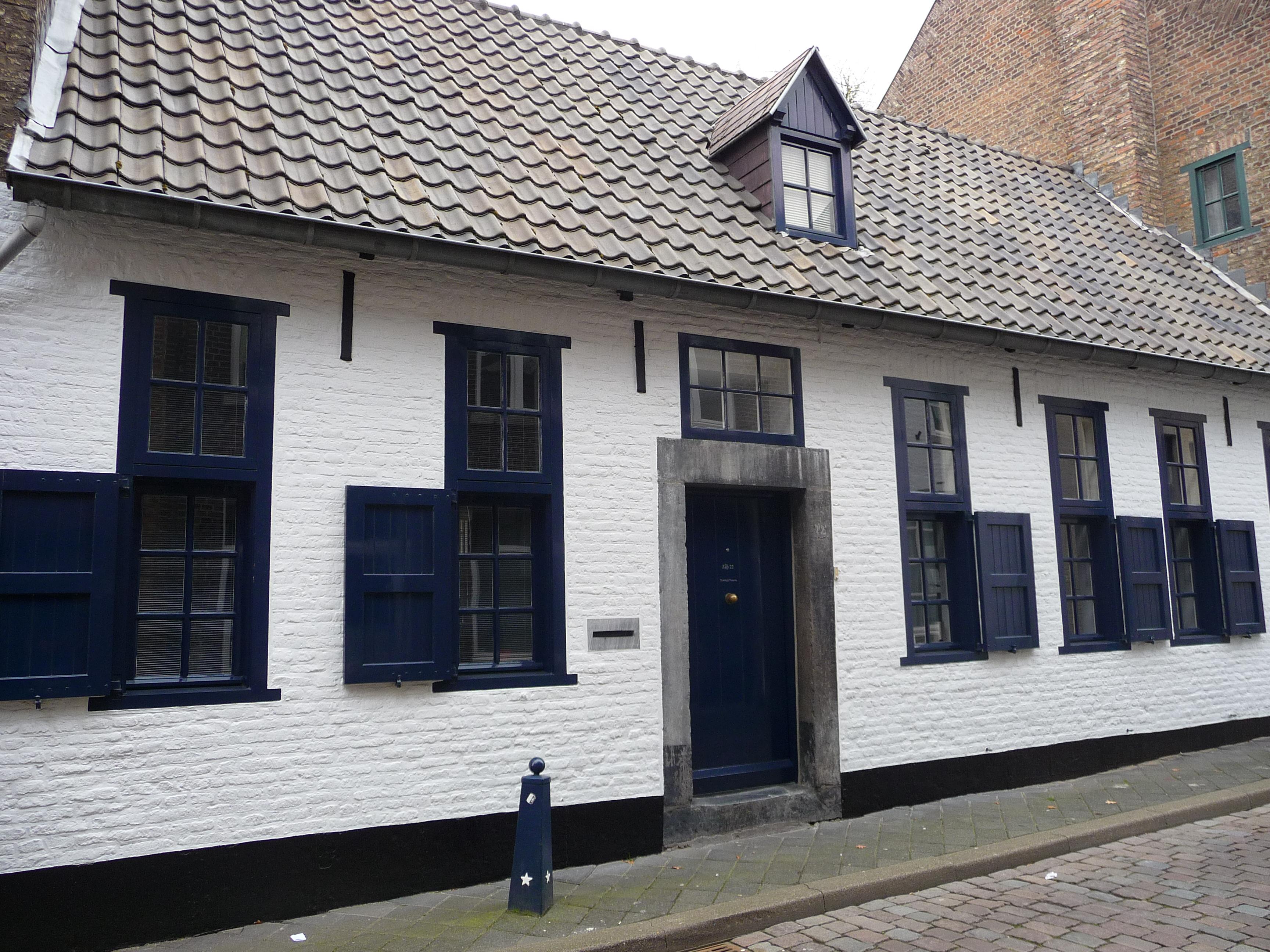 Laag huis met in de brede lijstgevel houten tussendorpelkozijnen en een ingang in naamse steen - Huis ingang ...