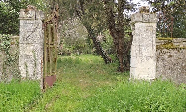 Château de la Noue, portail du jardin avec le mur de cloture, deux piliers et la grille en fer forgée, chapelle tout au fond à peine décelable, herbe au premier plan et foret dans le jardin