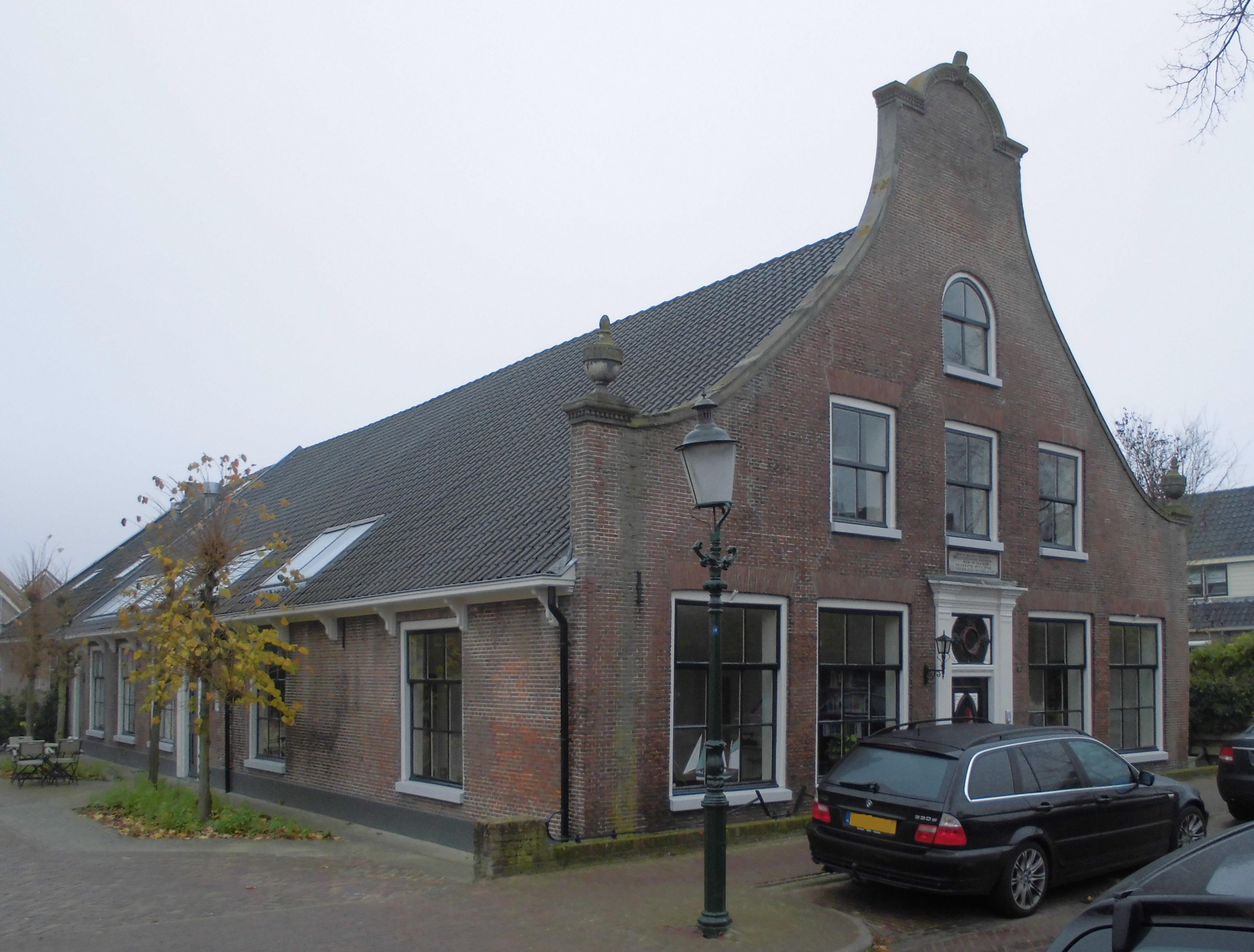 Langgerekte met oud hollandse pannen gedekte boerderij met voorname gevel in huizen monument - Gevels van hedendaagse huizen ...