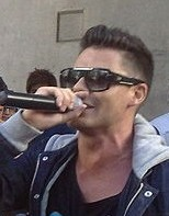 Man with spiked-up black hair and wearing black sunglasses and jacket singing into a hand-held microphone