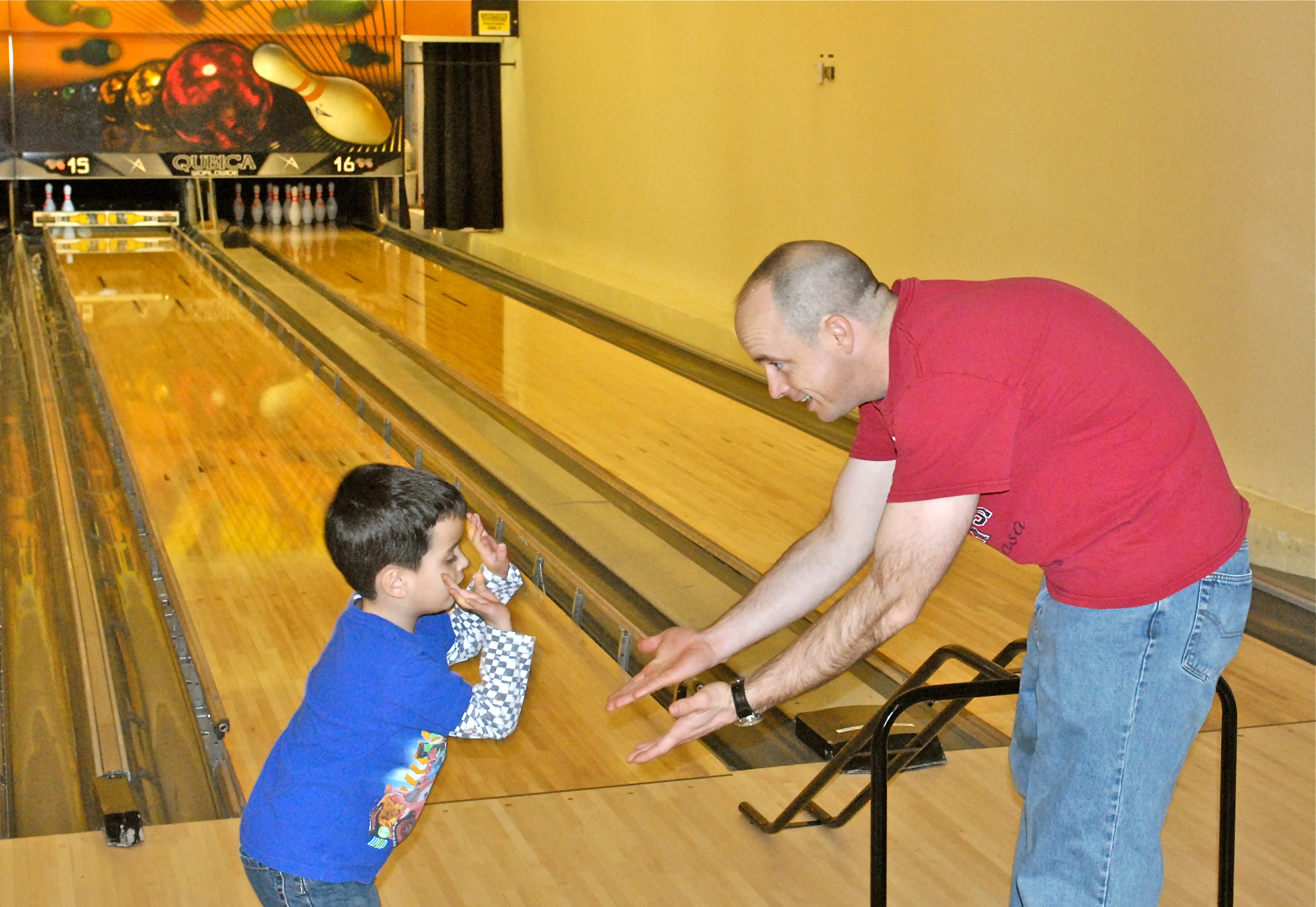 Man and boy high-fiving each other (Strike Zone Bowling Center, Camp Humphreys)