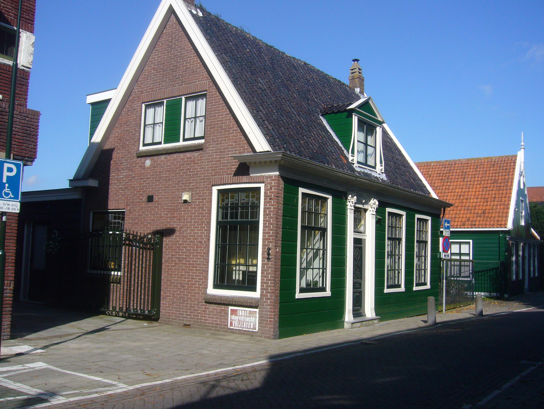 Grotendeels houten huis met zadeldak parallel aan straat ingang met bovenlicht tussen pilasters - Houten huis ...