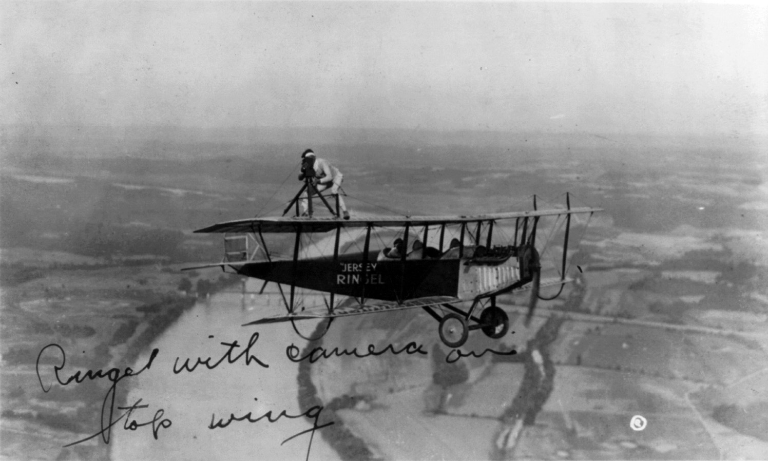 A man standing on top of wing of aeroplane fli...