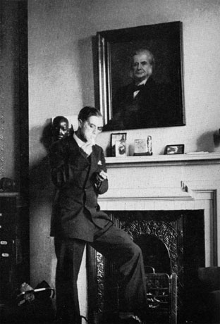 Huxley lights a cigarette under his grandfather's portrait, c.1935. Hux-cig-72.jpg