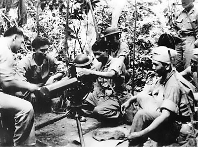 Group of cadets being trained by a Marine on usage of a water-cooled machine gun.