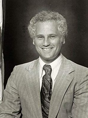 Black-and-white photo of a man with a wide smile and short curly hair wearing a light-colored suit