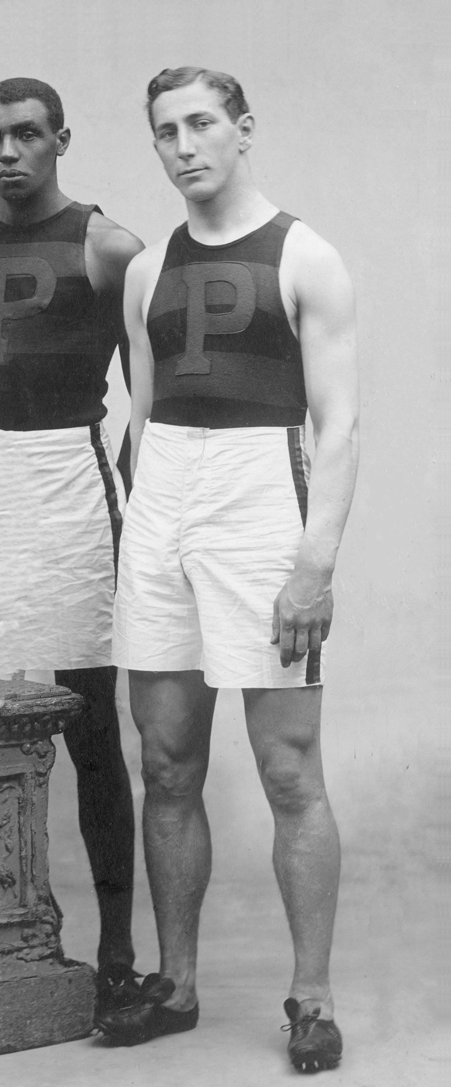 A white male stands and faces the camera in an older photograph. His right hand is behind his back. He is wearing a stripped sleeveless athletic top with a P on the front, white athletic shorts, and running shoes.