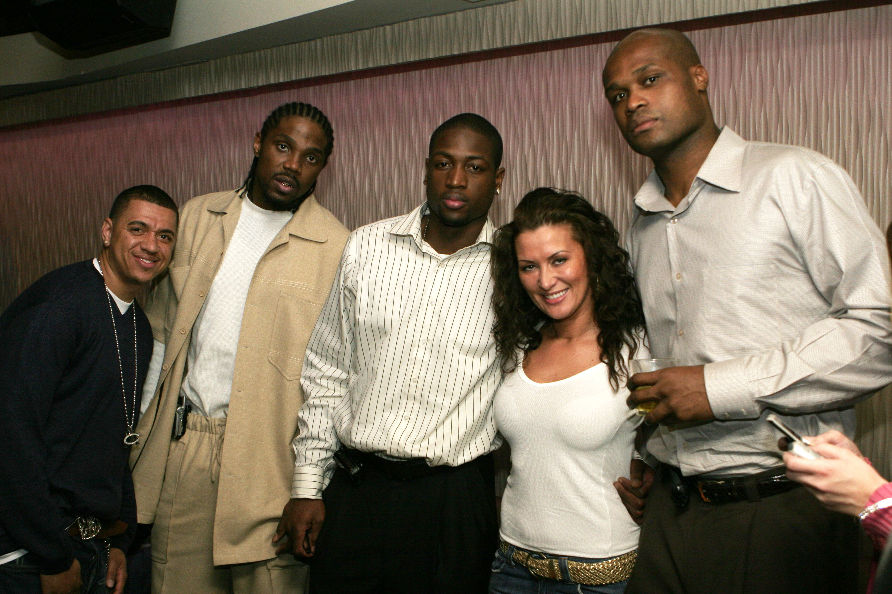 Wade at a party with teammate Udonis Haslem and former teammate Antoine Walker and others.