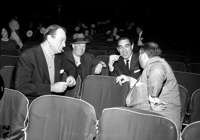 Jerry Wald (facing away from camera) during rehearsals for the 1958 Academy Awards, with [[John Wayne]], [[Maurice Chevalier]] and [[Anthony Quinn]]